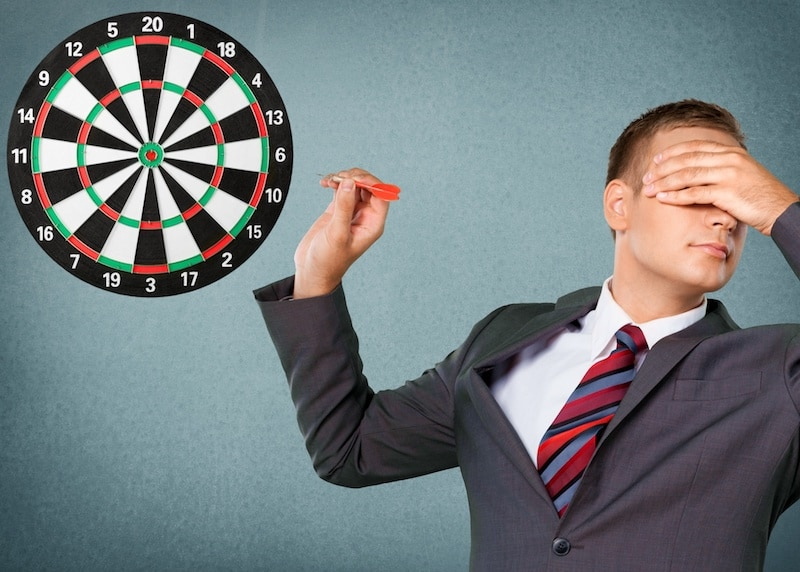 business owner throwing darts eyes closed instead of marketing consulting